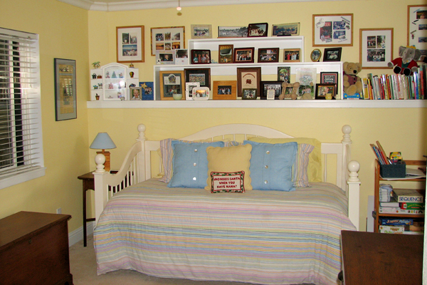 Family photographs above a daybed.  Martinez Home Tour.
